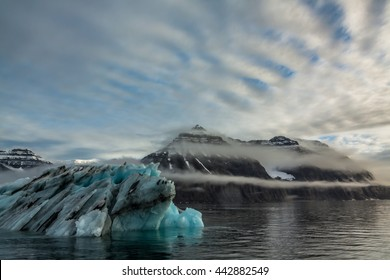 Iceberg in Greenland.  An iceberg or ice mountain is a large piece of freshwater ice that has broken off a glacier or an ice shelf and is floating freely in open water, heading out to sea.