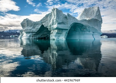 Iceberg in Greenland. No two icebergs are alike, and when you see an iceberg for the first time, you may be seeing shapes and sizes that no-one has seen before. This iceberg has several ice caves.