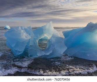 Iceberg with Hole, Ocean, and Clouds