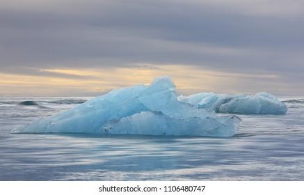 Iceberg from the Jokulsarlon glacial lagoon drifting  in the North Atlantic Ocean at sunset, Iceland. Shot on long exposure