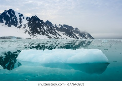 Iceberg and mountains are reflected in the blue water, calm and silence, Arctic landscape. Svalbard
