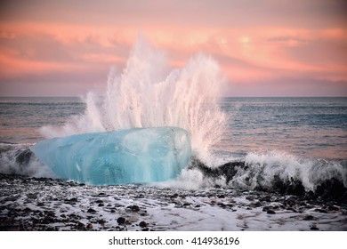 Iceberg on the black volcanic beach during sunset being hit by a violent wave