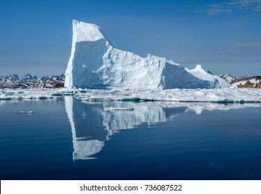 An iceberg reflect in the arctic sea in front of the coast of Greenland in white and blue colors
