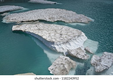 Icebergs broken off from a glacier in a glacial lake in the mountains