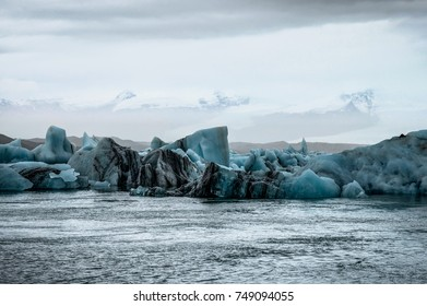 Icebergs floating in Jokulsarlon glacier lake at sunset in Icela