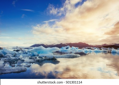 Icebergs in the glacial lake with a mountain in the south of Iceland at sunset. Jokulsarlon