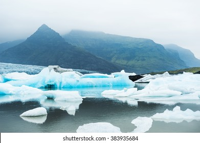 Icebergs in the glacial lake with mountain views. Vatnajokull glacier, Fjallsarlon lagoon, south Iceland