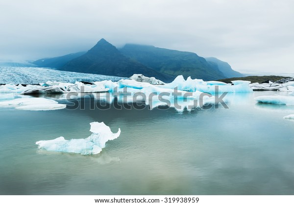Icebergs in the glacial lake with mountain views. Vatnajokull glacier, Fjallsarlon lagoon, south of Iceland