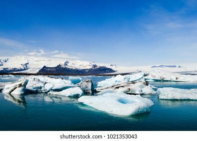 Icebergs in Jökulsárlón Glacier Lagoon Iceland blue sky green water