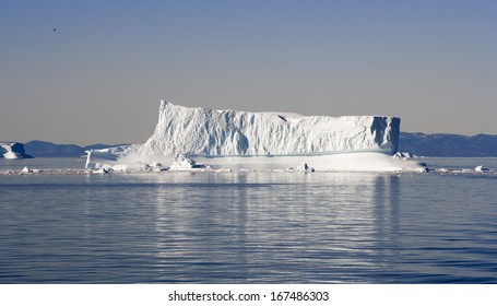 Icebergs of Greenland under a bright sun of polar summer. Deep pure waters of  northen seas.