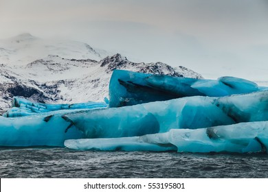Icebergs in Jokulsarlon glacial lagoon during a vibrant sunrise, Iceland
