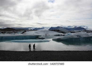 Icebergs at Jokulsarlon glacier with dark cloudy sky background and two tourists in silhouette at waterline