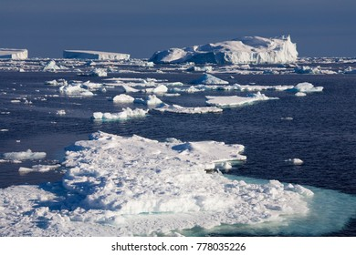 Icebergs and sea ice floating off the coast of the Antarctic Peninsula in the Weddal Sea in Antarctica.