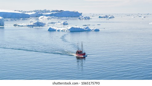 Icebergs and tourist fishing boat in Greenland iceberg landscape of Ilulissat icefjord with giant icebergs. Icebergs from melting glacier. Aerial drone photo of arctic nature.