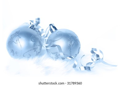 Ice-blue Christmas baubles and ribbon, on white fur.