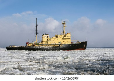 Icebreaker ship breaks ice and moves across the frozen sea