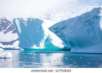 icecaps in the Antarctica with iceberg in the ocean swimming around and melting in the sea