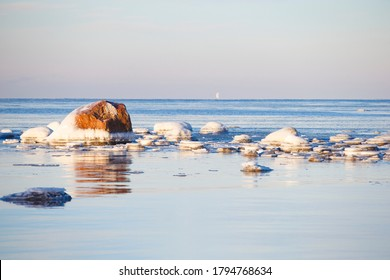 Ice-covered granite stones in the bay of the Gulf of Bothnia