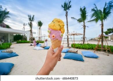 Icecream cone held on the beach with nice sky, Summer