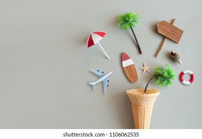 Icecream cone with various summer items including parasol, surfboard, miniature airplane and pine trees