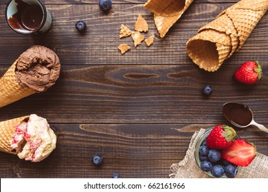 Ice-cream with fresh berries and chocolate sauce on the wooden background, top view. Copy space.