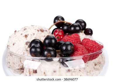 Ice-cream with fresh berries of a currant and a raspberry in a vase on a white background.
