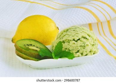 Icecream with lemon, kiwi and mint in porcelain dish.