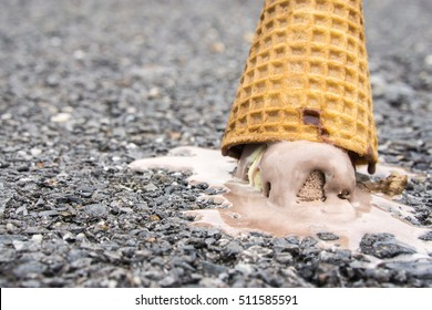 Icecream on the ground. (selective focus)., chocolate icecream cone dropped on the concrete floor and melt on ground. with copy space for text. dirty concept. lost concept.