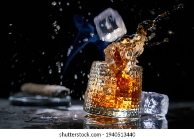 Icecube splashing to glass of whiskey. Copy space, black background. Smoking cigar and whiskey, brandy, cognac, alcoholic drink .