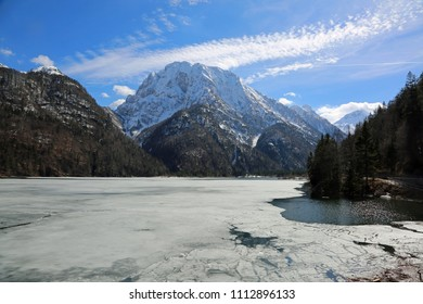 iced alpine lake called Lago del Predil in Italy near Tarvisio Town and mountains in winter
