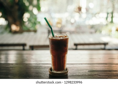 Iced Americano coffee with blur outdoor cafe table background