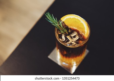 Iced americano or iced coffee with yuzu orange juice topped with rose mary leaves