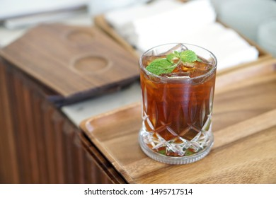 Iced black coffee mojito - A glass of Cold brew coffee mixed with brown sugar, tropical fruit and mint on blurred background, Barista making coffee cocktail, Perfect drink for summer time.