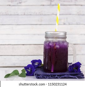 Iced butterfly pea flower juice on fabric against white wood background