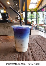 Iced butterfly pea milk on wooden table
