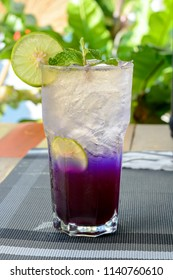 Iced butterfly pea tea with lemon and palm juice on wooden table. Relax with Thai herbal drink for healthy life in natural concept.