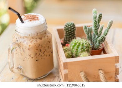 Iced cappuccino with cactus in coffee shop vintage color tone. Coffee and hobby concept. Close up and Soft focus.