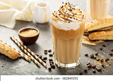 Iced caramel latte coffee in a tall glass with syrup and whipped cream.