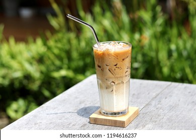 Iced caramel macchiato coffee beverage in glass with stainless steel straw for drink.  Concept for reduce plastic pollution and support green eco friendly products. selective focus
