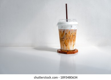 Iced caramel macchiato coffee in plastic cup on a wooden table at the cafe. Cold espresso in the coffee shop with copy space. Beverage glass frozen in the restaurant. Food interior decoration vintage.