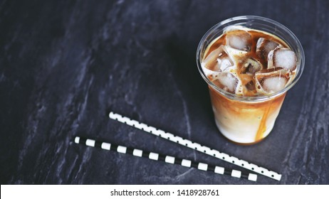 Iced caramel macchiato served in disposable transparent plastic glass on black stone background with blurred eco friendly paper straws. Theme for staying fresh, Refreshing and enjoying summer time.