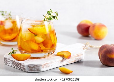 iced carbonated tea with peaches and mint in a glass on a gray background, horizontal