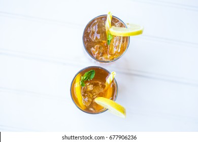 Iced Chilled Drink Tea Cocktail with Lemon Garnish and Yellow Straw on the Balcony White Background Top Down View