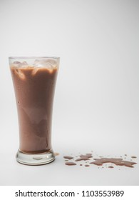 Iced chocolate or cacao in clear glass on white isolated background in side view with copy space. Concept to present bitter sweet and delicious drink.