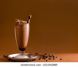 Iced chocolate coffee with wafer straw on plain brown background