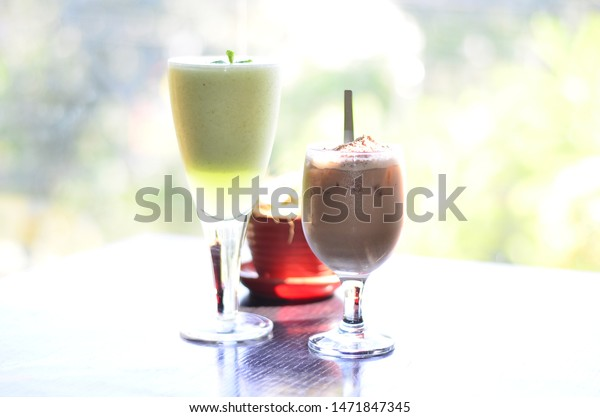 Iced chocolate drink and fresh melon juice served on a table by the window