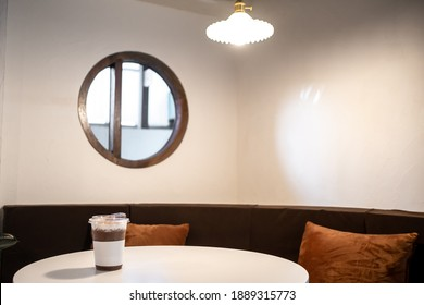 Iced chocolate on plastic mug cup on wooden table in Cafe shop mood minimal interior design Blur background. Minimalistic Scandinavian interior