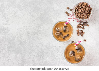 Iced cinnamon coffee on concrete background. Top view, copy space.