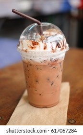 Iced coco or chocolate with straw in plastic cup in coffee shop