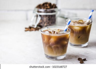 Iced coconut coffee in glass and coffee beans in glass jar on white background. Selective focus, copy space.